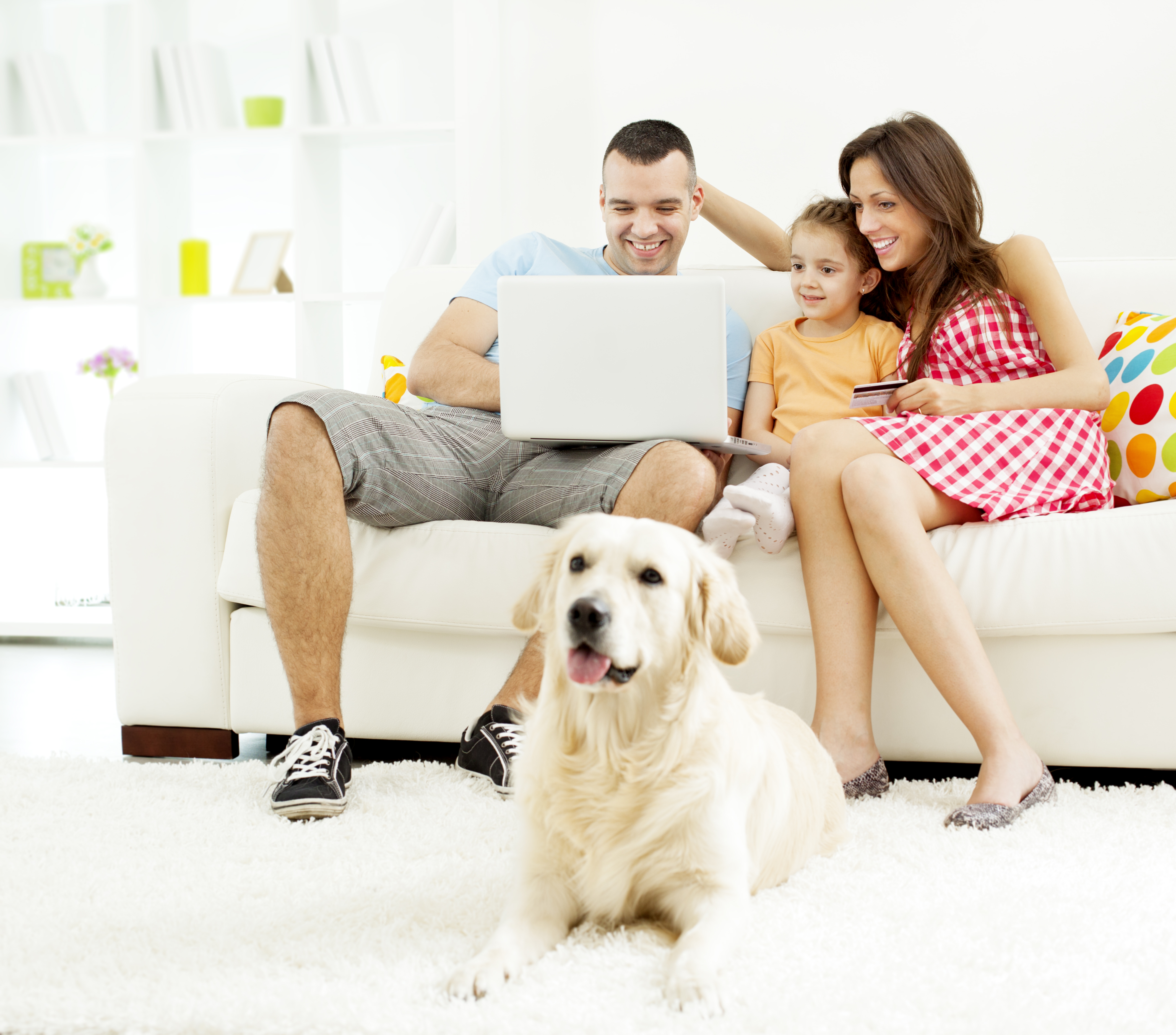"""""""Family with one child shopping online together. Sitting on sofa, mother holding credit card and father holding laptop and looking for his daughter wishes. Selective focus to father and daughter. Their dog, Retriever, lying in front of them on the carpet."""""""